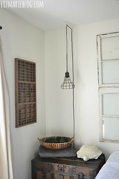 Industrial wire pendant, vintage printer press drawer, antique trunk nightstand, & antique window headboard. Great vintage touches in a guest bedroom!