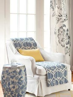 """""""This slipcovered seat got a facelift—fast—via a folded, lightweight cotton rug.""""    Read more: Cheap Living Room Decorating Ideas - Decorating a Living Room on a Budget - Country Living"""