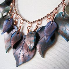 Here is a distinctive bib necklace displaying a cascading design of hand-sculpted, polymer clay leaves in an assortment of sizes, hanging from a