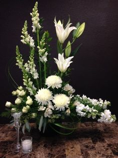 White Tribute-   This lovely sympathy arrangement in all white is one of our most popular. Make the most at the celebration of life or if you prefer we can send this sympathy to the home with long lasting orchids, gerbera daisies and lilies. Approximately 21in W x 37in H One-Sided White Tribute White PJ's Flowers & Events Tony Medlock