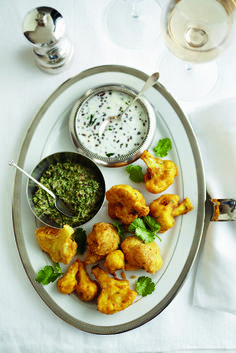 These cauliflower fritters are an excellent pre-dinner bite, and are fantastic when paired with the spiced yogurt and a mint chutney.