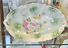 ITEM # 21511   Rare and scarce deep oblong two handled bowl.   It is 12 3/4 in length, 8 in width and sits 2 1/2 tall.   This mold found in Mary Frank Gastons 4th series Collectors Encyclopedia of RS Prussia. RS Steeple mold 8, companion mold to RS Russia mold 343 with floral decoration transfer of a yellow rose, and pink white and lavander wild flowers.   No chips, cracks, or repairs, very slight gold loss due to age and handling. Very good antique condition!   PLEASE let me know i...