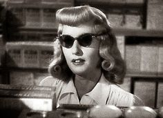 Barbara Stanwyck in 'Double Indemnity,' with the rolled bangs and very dark glasses of the 1940s femme fatale.