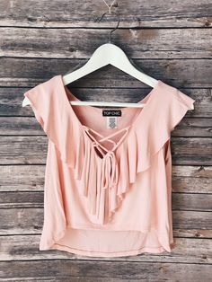 """Cute jersey knit crop top features a lace up closure, ruffled detail on front and flutter sleeves. Fabric Content: 95% RAYON 5% SPANDEX Description: L: 18"""" B: 44"""" W: 40"""""""