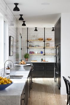 Rejuvenation Jefferson Flush Mount lighting beams in this modern kitchen with white subway tiles + black cabinets.