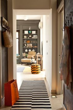 @Annette Joseph place in Italy: grey built ins, black and white stripe runner rug, mustard armchair, cute pouf