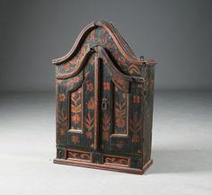 Lite rosemalt hengeskap med to dører og skuff. Eierinitialer og datering 1794. Malt også på sidene. H: 76 cm. B: 51 cm. En ny list. Prisantydning: ( 15000 - 20000) Tilbake