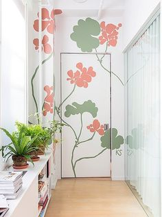 "In a hallway connecting the master bedroom to the living room, Kate transformed a seldom-used door with a mural of geraniums painted in her signature larger-than-life scale, creating ""a nice focal point."" She adds, ""I never sketch my murals. They're always improvised in the moment… I'll climb up a ladder with a bunch of plants or flowers nearby and paint how I see them up on the wall."""