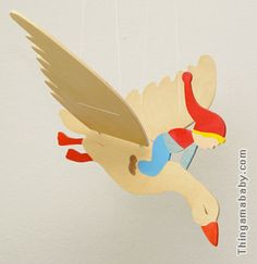 Photo of a wooden mobile depicting a boy wearing a long red cap who is riding a flying goose.