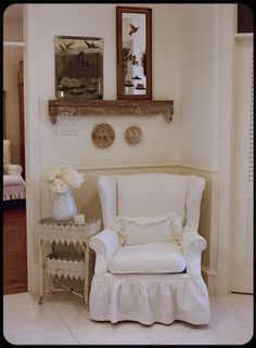 The Old Painted Cottage Unique Goods and Curious Finds| white slip covered wing back chair with ruffle. Small side table. Shelf above. For the foyer.