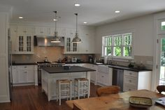 source: MSM Property Development  Gorgeous open kitchen with white glass-front kitchen cabinets, white square kitchen island, soapstone counter tops, Pottery Barn Napoleon Backless Bar stools, industrial polished nickel yoke pendants, beige crackled subway tiles backsplash and farmhouse sink.