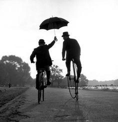 Chauffeur and Master, Ken Russell, 1956 bicycles, friends, umbrellas, bike, pennies, ken russel, black, rain, photographi