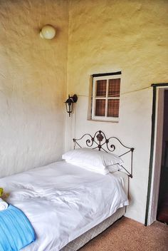 The Post office at Stormsvlei Riverside Cottages. Simple bedroom. Steel headboard.