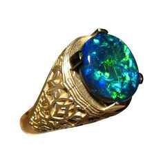 An outstanding Black Opal ring for men with a large Black Opal set in a detailed 14k Gold ring.