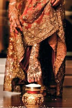Note the Henna work [mehndi] on the feet and hands of the indian bride. She is entering her new house for the first time after the wedding. and has to topple the rice at the entrance before she goes in. Big Fat Indian Wedding, Indian Bridal Wear, Indian Weddings, Bridal Henna, Bollywood, Indian Dresses, Indian Outfits, Indian Aesthetic, Naeem Khan