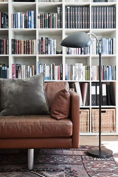 Leather couch + vintage kilim + bookshelf = inspiration for our living room. {via Hunch}
