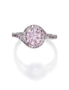 PLATINUM AND FANCY INTENSE PURPLISH PINK DIAMOND RING Centered by a round Fancy Intense Purplish Pink diamond weighing 1.06 carats, accented by small round diamonds of pink hue weighing approximately .30 carat