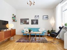 Living room with turquoise sofa as centerpiece and scandinavian decor.