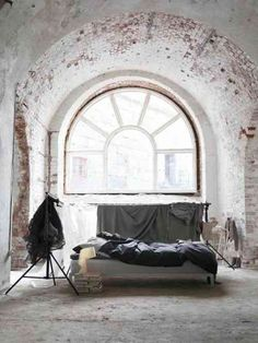 Une chambre avec des briques peintes en blanc