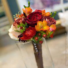 A simple autumn bouquet of red roses, blush Sahara rose, red ranuculus, orange freesia and Tiramisu spray roses