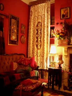 red room with bookcase hidden behind a curtain