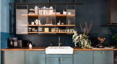 Blauwe keukenkasten en houten planken met glas ervoor met zwart frame in industriële stijl in een donkerblauwe keuken.
