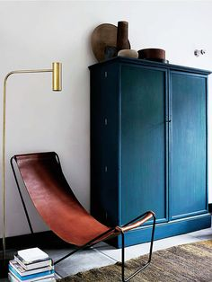 dark teal cabinet, cognac leather sling chair and brass reading lamp