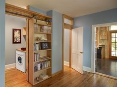 Sliding bookcase on salvaged barn track to conceal laundry room.