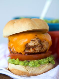 Turkey Chorizo Burgers with Guacamole  pound ground turkey 1/2 pound chorizo sausage 2 avocados, pit removed 1/4 medium red onion Juice of 1 lime 1/2 tsp. salt 1/2 tsp. pepper 4 buns, cut in half and toasted 4 slices of cheddar cheese (or whichever cheese you prefer to use) 4 slices of tomato