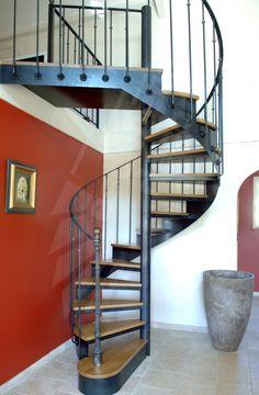 Photo DH45 - SPIR'DÉCO® Bistrot sans contremarche - modèle déposé. Escalier intérieur hélicoïdal métal et bois. Cet escalier en fer forgé, avec son look 'fin XIXème siècle', sa rampe ornée, la chaleur de ses marches bois, s'intègre dans tout type d'intérieur avec charme et caractère. Limon formant crémaillère en tôle roulée. Option 1ère marche arrondie et débordante formant podium de départ + poteau décoratif en fonte moulurée avec boule acier en tête. Finition : Acier brut patiné.