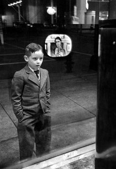 A boy watches TV in an appliance store window in 1948. Ralph Morse.