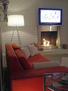 A Modern Twist ~~ Covering the old red brick, white paint instantly adds a modern touch to RMS user fjames74's living room. The stainless steel fireplace surround enhances the contemporary look.