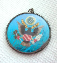 WWII ERA BUTTERFLY WING SILVER PATRIOTIC PENDANT WITH US SEAL + FLAG  This is a very unique piece of butterfly wing jewelry. It is a fairly large, about 1 1/2 inch across. One side shows the Great Seal of the United States over butterfly wing and, the other, a hand-painted US flag over butterfly wing. It appears that real feathers were used in making the eagle. This is so neat because it's collectible in several ways: Military, folk art, vintage jewelry... Wow!  US $75.00 on ebay
