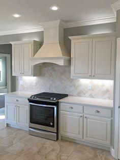 White kitchen with satin nickel fixtures, pendant lights, travertine backsplash, white quartz countertops, wood range hood