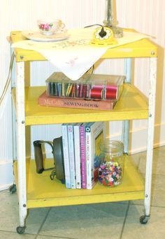 Vintage LEMON YELLOW and WHITE chippy shabby cottage rolling kitchen shelf storage cart with wheels three tiers shelves. $65.00, via Etsy.