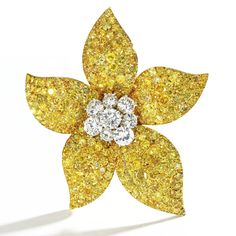 18 KARAT GOLD, COLORED DIAMOND AND NEAR COLORLESS DIAMOND FLOWER BROOCH, VAN CLEEF & ARPELS, FRANCE, CIRCA 1960 Set in the center with near colorless round diamonds weighing approximately 4.50 carats, the petals set with round diamonds of yellow hue weighing approximately 20.00 carats, signed Van Cleef & Arpels, numbered MC 632, French assay marks.