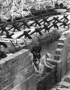 Das Archivbild vom 26.05.1962 zeigt Bauarbeiter, die unter der Bewachung von DDR-Grenzpolizisten Sprengstoffschäden an der Berliner Mauer in der Bernauer Straße/Ecke Schwadter Straße beseitigen. Eine Sprengstoffanschlag kurz nach Mitternacht hatte ein zwei Meter breites Loch in die Mauer gerissen