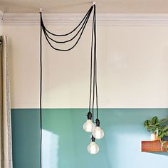 DIY hanging pendants have a look found in high-end decorating but are much less expensive. To kick off this modern update, remove the aluminum shade and clamp from three $7 portable work lights. Edison bulbs and exposed cords keep with the room's casual decor.