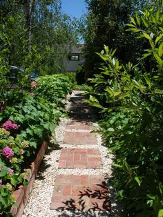 Brick in pea gravel around raised garden beds