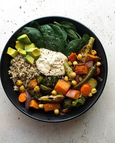 "ROASTED NOURISH BOWL Ingredients olive or coconut oil, 1 - 2 tablespoons 1 large sweet potato, cut into 3/4"" cubes 2 large carrots, sliced 1 1/2 cups brussles sprouts, 1 1/2 cups broccoli florets 1/2 large red onion, sliced 6 serrano chilis, 1 1/2 cups cooked chickpeas or 1 can (15oz) 1 - 2 lemons, cut into six pieces To serve 1 1/2 cups cooked quinoa 5 oz. spinach 1 - 2 avocados big dollop of hummus red pepper flakes, to garnish"