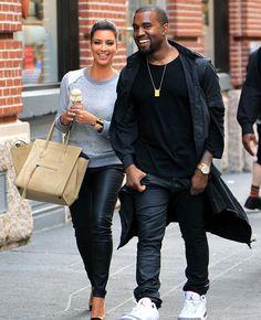 Kanye West & Kim Kardashian . Tan Flawless Skin , Hair Back , Casual Sweater , Big Bag , & Small Diamond Earrings