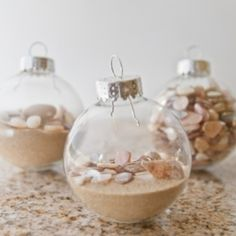 A summer tree is decorated with diy ornaments filled with summer sand, shells, and small stones.