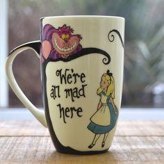 This fine bone china mug stands tall and is hand painted with an Alice in Wonderland design. It features the Cheshire Cat, Alice and a quote from the book on the reverse and comes boxed as shown. Disney Coffee Mugs, Disney Mugs, My Coffee, Coffee Time, Coffee Cups, Coffee Art, Coffee Beans, Tea Time, Drawing Coffee