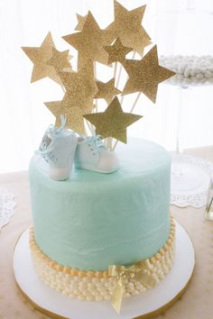 Torta de baby shower decorada con estrellas y zapaticos de bebe. #PastelDeBabyShower