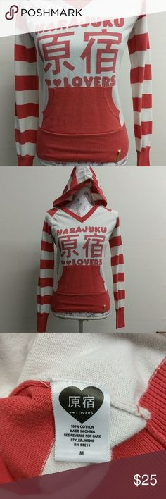 Harajuku Lovers Hooded Sweater 100% cotton hooded sweatshirt in coral and white. Has front pocket. Has stripes on sleeves and on the back. Harajuku Lovers by Gwen Stefani. Coral color is a red/orange color. Harajuku Lovers Sweaters