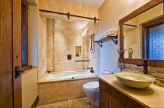 carrelage travertin, vasque à poser, meuble de rangement en bois massif et miroir rectangulaire