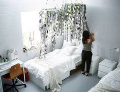 Strips of fabric tied to hula hoops and hung above a bed.
