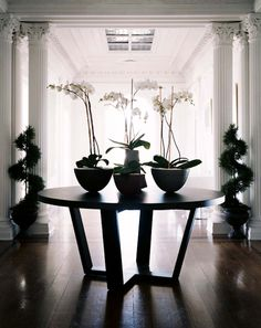 Erinn V Design Group: Chic grand entrance foyer design with modern round table, Greek columns and orchids.