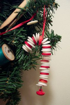 Old Button Candy Cane Ornament, Old buttons strung on floral wire. Use needlenose pliers to bend wire in loop at bottom hang decorative button or bell at the bottom . Then string white and red buttons thru their eye holes on wire. Bend end of wire back thru second hole in last button to hold on. String with ribbon and you have it!, Holiday Project