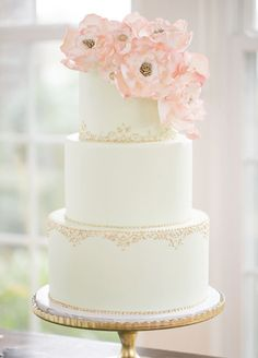 10. The classic white wedding cake gets a vintage touch from gilded detailing and lush sugar blooms.